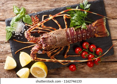 Preparation for cooking food spiny lobster or sea crayfish with fresh ingredients close-up on a wooden table. Horizontal top view from above