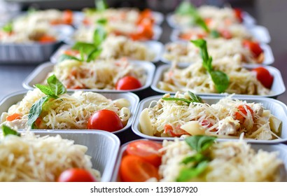 preparation of dietary dishes in the kitchen for the delivery of dietary lunch, basil, tomato cherry, cheese, pasta and chicken fillet. concept of takeaway food. selective focus