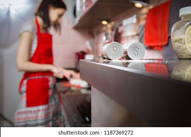 Preparation of dinner. Salt and pepper against the background of a young girl who cooks a dish on a black table in the kitchen.