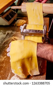 Preparation of the dough, with an electric machine, to make fresh homemade pasta. Rolling a dough through a pasta machine