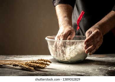 Preparation of the dough. Preparation of the dough the men's hands. On a wooden table. Food concept.
