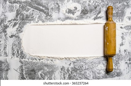 Preparation of the dough. The rolling pin with flour on a stone background. Free space for text. Top view