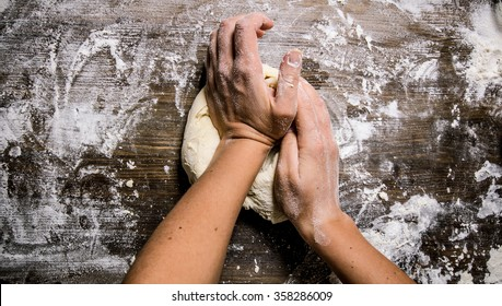 Preparation of the dough. Preparation of the dough the women's hands. On a wooden table.  Top view