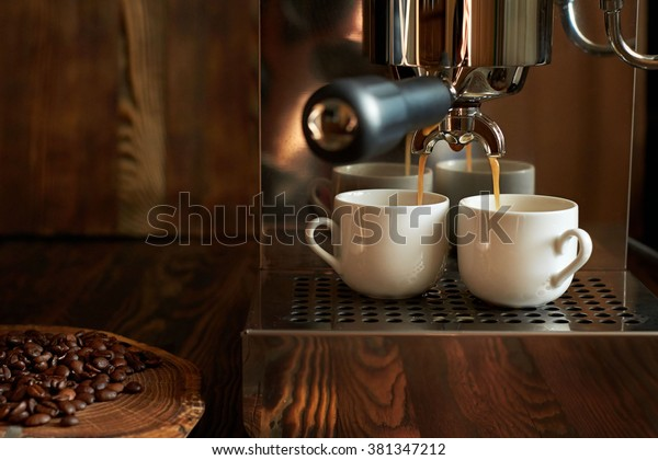 Preparation of espresso in a coffee machine. A jet of coffee being poured into white cup.