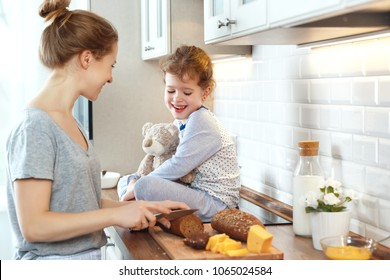 preparation of a family breakfast. mother and child daughter cut bread and cheese in morning