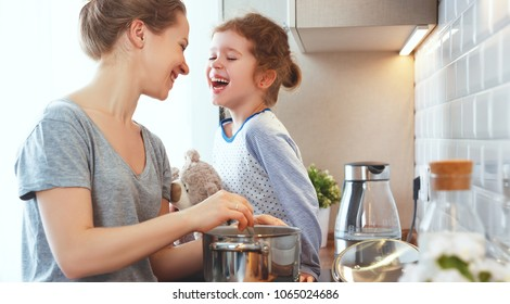 preparation of a family breakfast. mother and child daughter cook porridge in morning