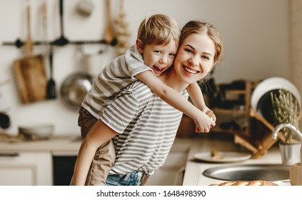 preparation of a family breakfast. mother and child son cut bread and eat cookies with milk in morning