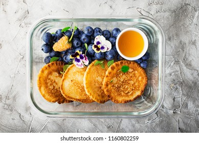 Preparation of food: ready breakfast with you: whole-grain fritters with blueberries, honey and edible flowers in glass containers. Top View