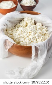 Preparation fresh cottage cheese with cheesecloth in wooden bowl. Close-up view, selective focus