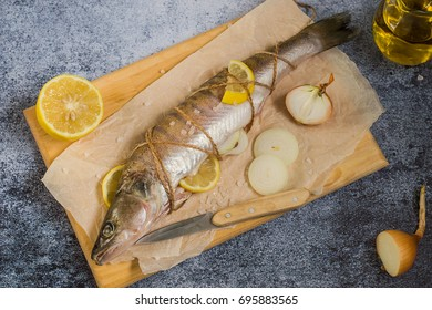 Preparation of fresh fish for baking. Raw zander, lemon and onion on a kitchen cutting board on a dark background. Selective focus.