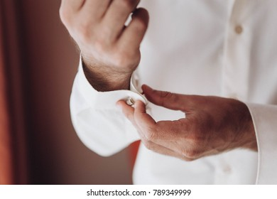 preparation of the groom for the wedding, the groom puts on the cufflinks on the shirt