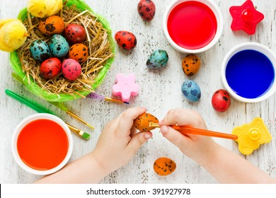 Preparation for happy Easter holiday. Child hands painting decorative colorful eggs, handmade Easter craft top view