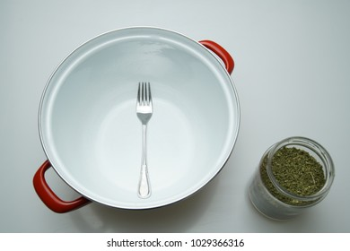 Preparation for home production of medical cannabis oil with big metal pan for mixing, grinned cannabis in glass jar and fork top view