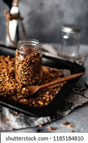 Preparation of homemade granola. The tray and filled a glass jar for storage. Vegan product. Selective focus