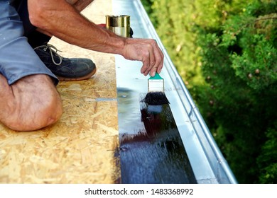 preparation for installing tar foil on the rooftop of building. Roofer cover the rooftop polymer modified bitumen waterproofing primer, with a paint brush. Waterproof system by gas and fire torching.