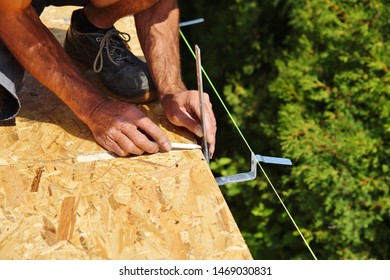 preparation of iron brackets of a roof gutter which are screwed on construction site.male Hand of carpenter holds a tool.gutters water drainage system.roofer installs roof gutter system. spirit level.