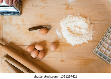 Preparation of Italian agnolotti with flour, eggs, rolling pins and a pasta cutting wheel on a wooden cutting board
