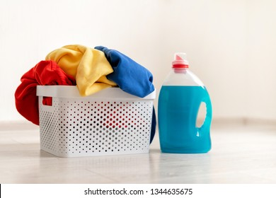 Preparation to laundry process. Close up photo of gel soap bottle standing on laminate floor inside flat with bright interior near basket with colorful clothes