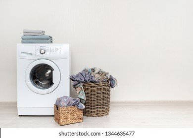 Preparation to laundry process. White washing machine with two basket with lien on floor and few towels on top standing isolated inside bright apartment light interior