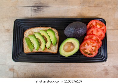 Preparation to make avocado toast with tomatoes and green onions on multigrain bread.