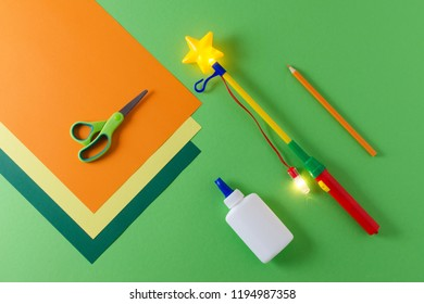 preparation to make diy lantern for sankt martin, traditional german feast, color paper, glue, scissors, lanterns wand with light on green background