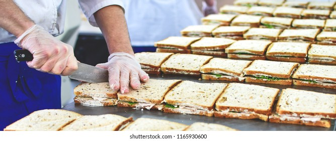 preparation of many sandwiches in the kitchen of the restaurant takeaway, the chef cuts the sandwich diagonally