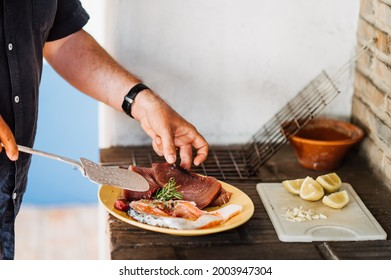Preparation of Mediterranean tuna fillet and salmon for grilling. One hand puts the fish on a lifter. Lemons and grill grate lie in the background. Selective sharpness, very shallow depth of field