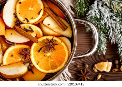 preparation of mulled wine in pot wooden background top view