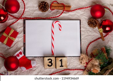 Preparation for new Year. Christmas decor laid out on paper surface. Fir branches, red ball, figures on the cube calendar 31, toys and decor. Top view and copy space. Flat lay.