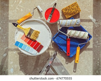 Preparation for painting works. Banks with paint, brushes and rollers are on the concrete floor. Home repair. The image is suitable for advertising a store of construction products