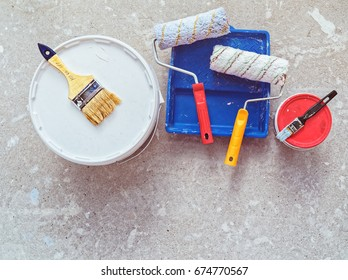 Preparation for painting works. Banks with paint, brushes and rollers are on the concrete floor. Home repair.