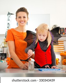 Preparation for a party is in full swing. Little blond girl in halloween bat costume spending time with mother in decorated kitchen. Traditional autumn holiday