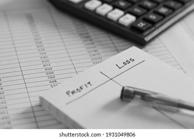 Preparation of profit and loss statement concept. Handwritten blank chart in notepad laid on roughly prepared balance sheet. Selective focus on the text LOSS.