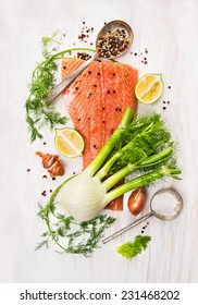 Preparation with raw salmon fillet,fennel, dill, lemon and onion on white wooden background, top view