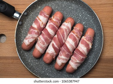Preparation of raw sausages wrapped spirally in bacon on a frying pan. Top view.