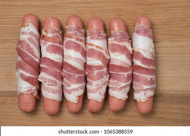 Preparation of raw sausages wrapped spirally in bacon on a wooden background. Top view.