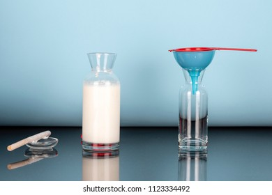 Preparation for separation of mixed organic probiotic milk kefir grains and fermented milk, two glass bottles one with fermented milk other empty with a red strainer on a blue funnel, blue background