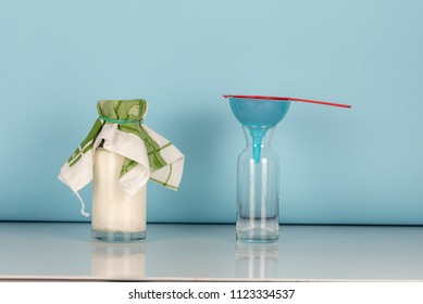 Preparation for separation of organic probiotic milk kefir grains and fermented milk, two glass bottles one with fermented milk other empty with a red strainer on a blue funnel, blue background