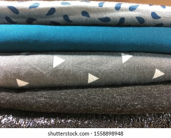 Preparation for sewing or crafting. Folded fabrics in stripes, solids, dots patterns. Textiles prepared for garment construction.