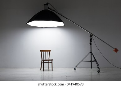Preparation for studio shooting: empty chair and studio lighting in white room