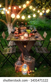 Preparation for supper with wine in illuminated summer garden