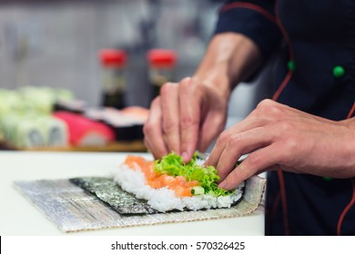 Preparation of a sushi roll in restaurant, close up on chef hands