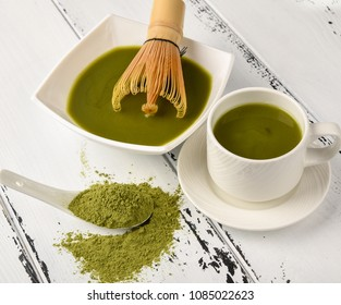 Preparation of tea match: bowl with whisk and tea cup, Green tea match powder in a white ceramic spoon