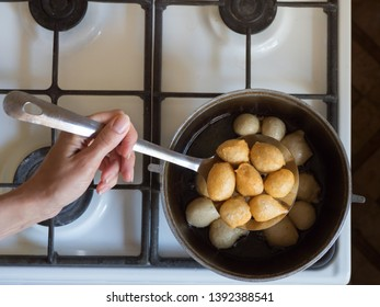 Preparation of traditional Greek sweets Loukoumades from dough with honey syrup.