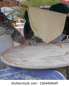 Preparation of a traditional Turkish yufka for pastries – Traditional Turkish food culture or cuisine. Woman making gozleme on turkish street market