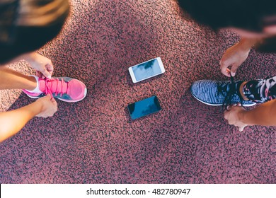 Preparation for the  training. Runner women tying running shoes laces getting ready for race on run track with smartphone.