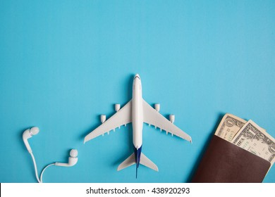 Preparation for Traveling concept, airplane, money, passport, earphone, book, on blue background with copy space.