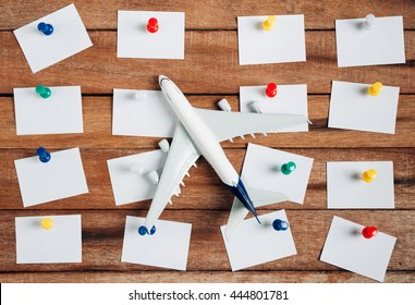 Preparation for Traveling concept and to do list, the paper noted, airplane, colorful push pin, on a vintage wooden background with copy space.