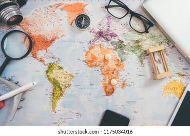 Preparation for Traveling concept, pencil, watch, money, airplane, noted book, earphone, on a vintage wooden background with copy space.
