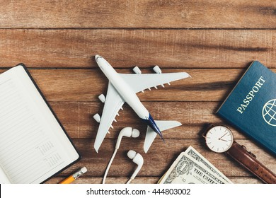 Preparation for Traveling concept, pencil, watch, money, passport, airplane, noted book,  earphone, on a vintage wooden background with copy space.